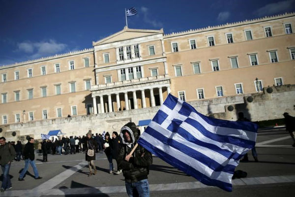 A farmer waves a Greek national flag in front of the parliament building during a demonstration to demand tax reductions and compensation, in Athens, Greece February 14, 2017. REUTERS/Alkis Konstantinidis