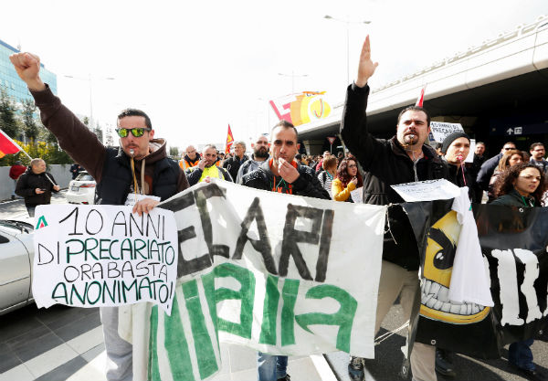 Alitalia employees take part in a protest at Rome's Fiumicino international airport in Rome, on Feb. 23. The banner on the left reads: