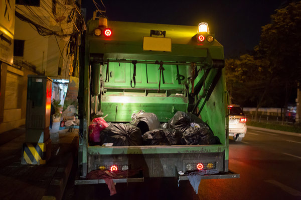Worker killed after being pinned between garbage trucks